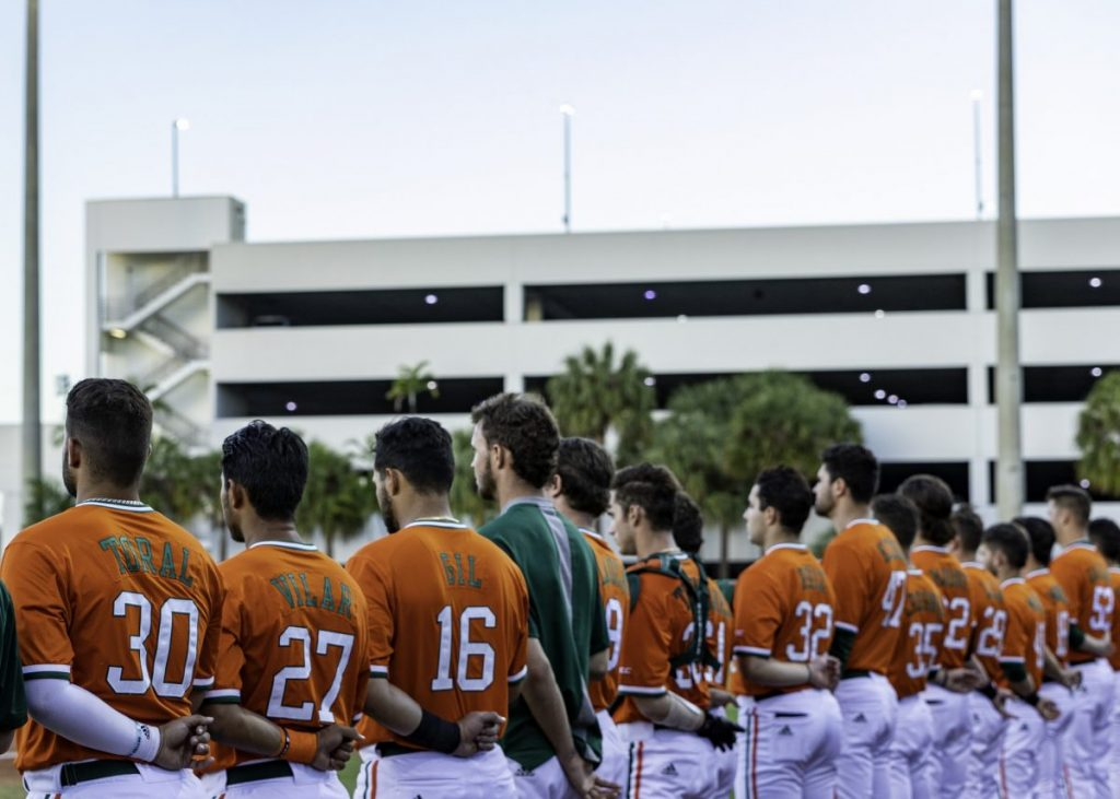 Members of the Hurricanes Baseball team line up for the national anthem before their game versus Kent State on Feb. 19, at Mark Light Field in Coral Gables, FL.