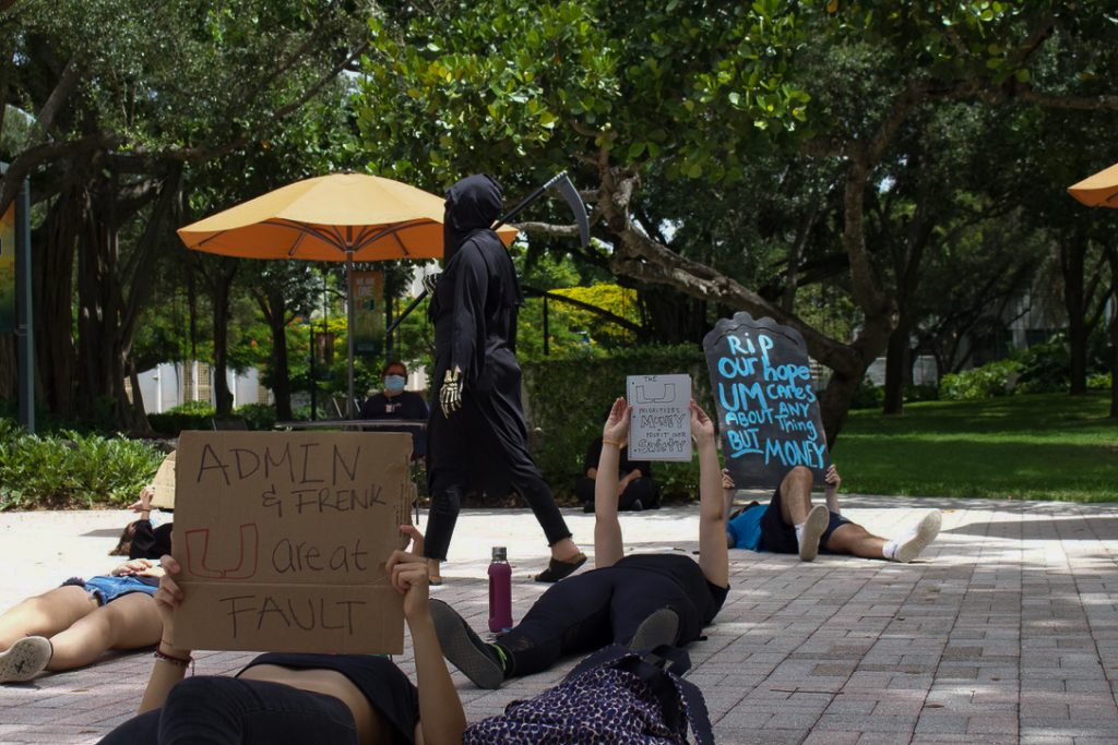 "Members of the UM community hold up ""gravestones"" and dress in all black on Friday, Sept. 4 at the Rock Plaza. Students and staff protested to raise awareness about issues with university actions during the COVID-19 Pandemic."