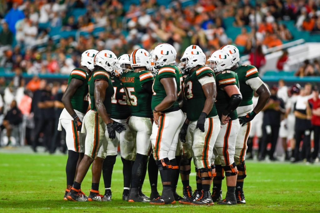 'Canes football players huddle during Miami's game versus Louisville at Hard Rock Stadium on Nov. 9, 2019. The Hurricanes beat the Cardinals 52-27.