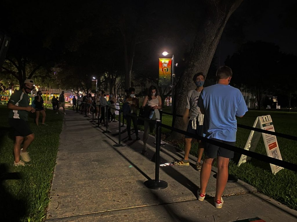 "Students wait in line to watch the presidential debate on the Foote Green on Tuesday, Sept. 29, 2020. The first 100 attendees received a free beach mat, beach towel, and a ""Canes Vote"" wristband."