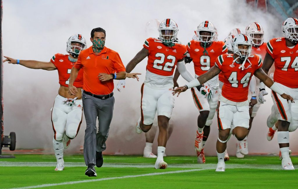 Coach Manny Diaz runs out of the tunnel with the team as the University of Miami hosts the UAB Blazers at Hard Rock Stadium in Miami Gardens on Sept. 10.
