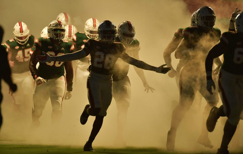 'Canes football players run on the field before playing Florida State at Hard Rock Stadium on Sept. 26.