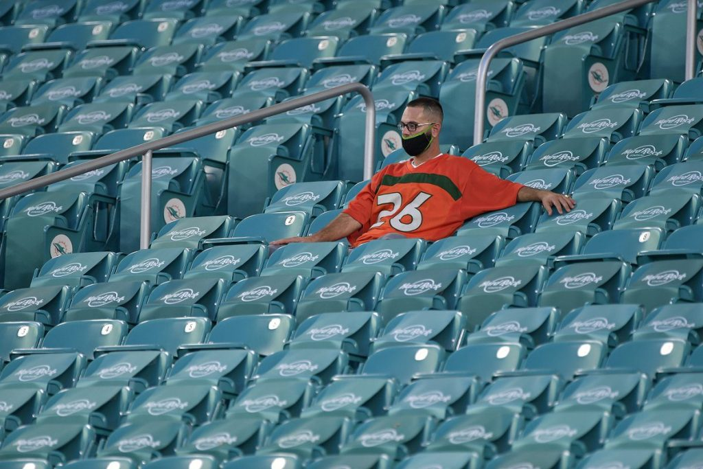 A Hurricanes fan practices social distancing while watching the 'Canes take on the UAB Blazers at Hard Rock Stadium on Thursday, September 10.