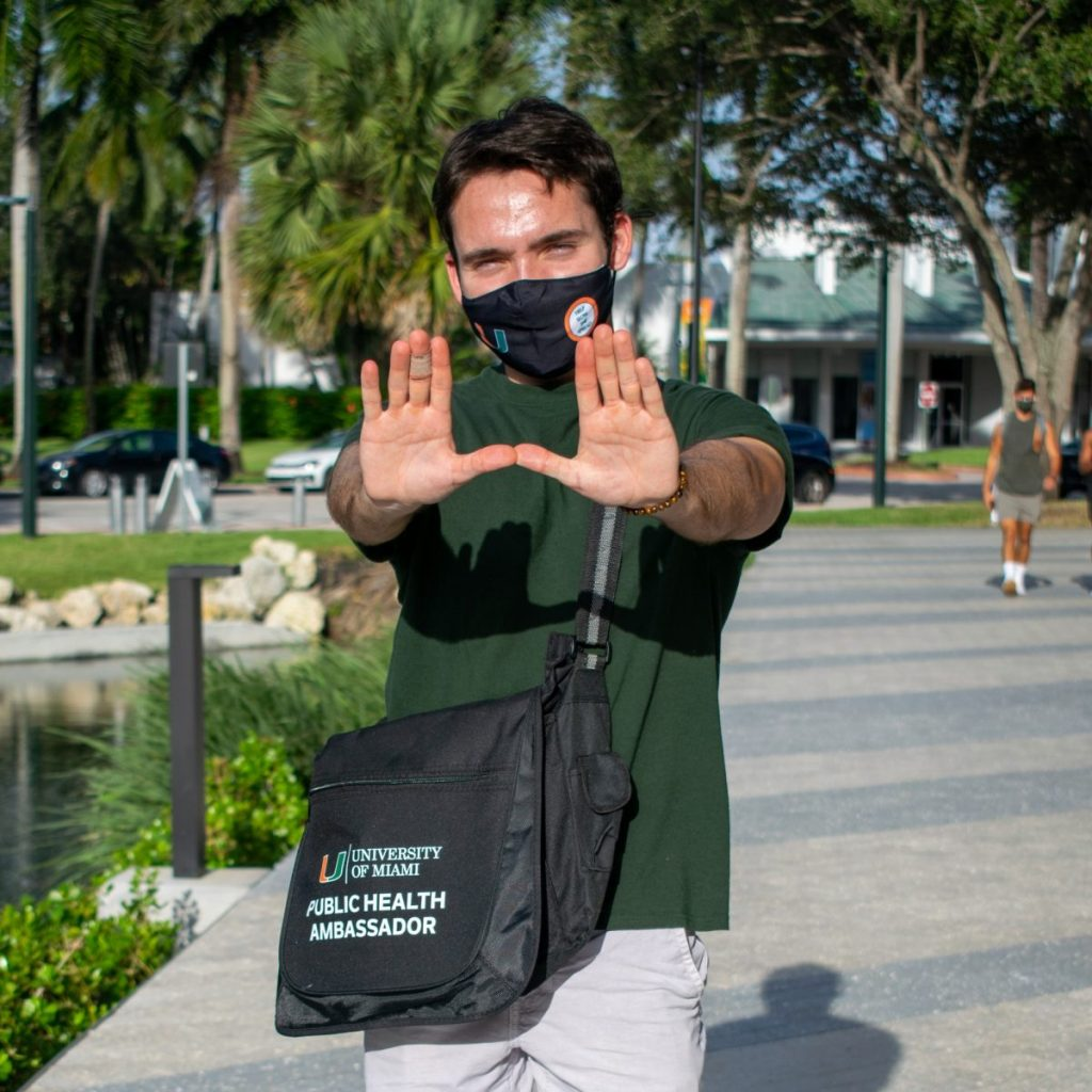Junior Chase Anderson, a Public Health Ambassador, throws up the U near Lakeside Village on Sept. 26.