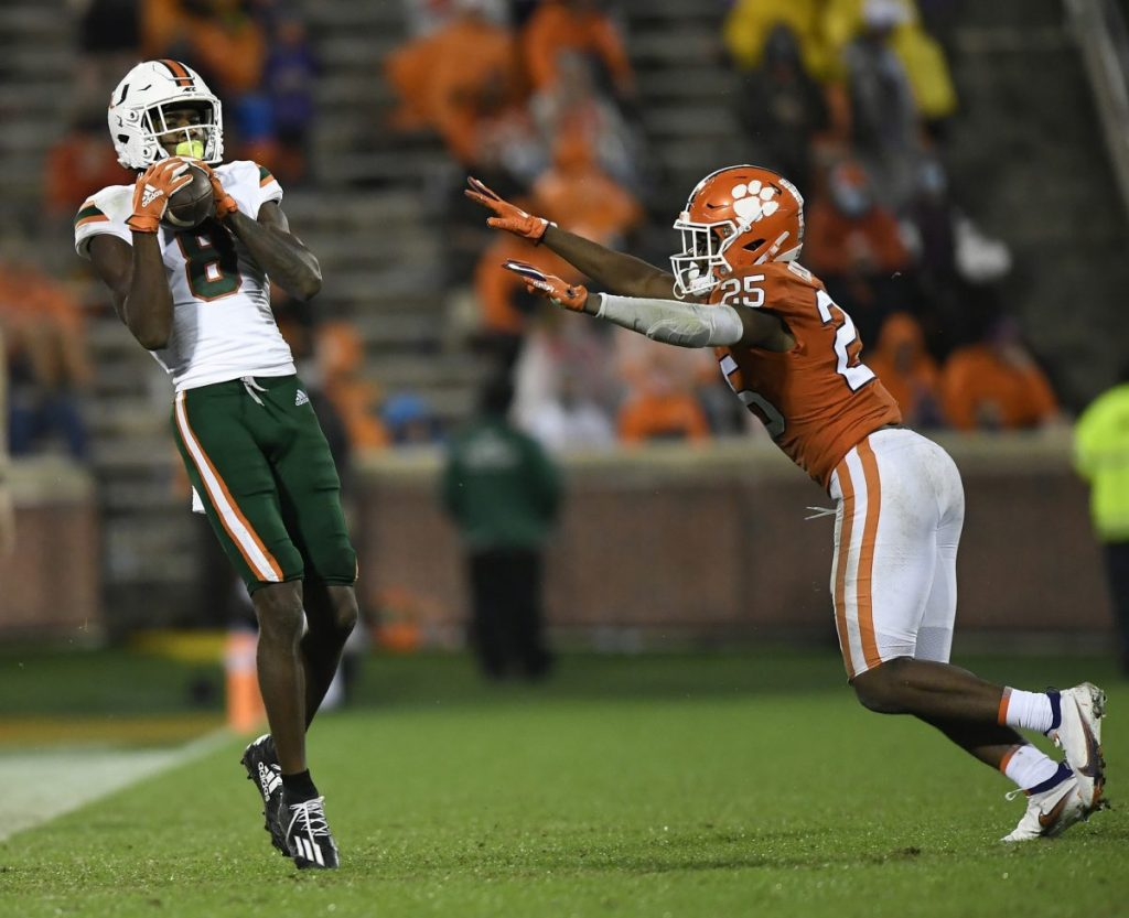 Wide Receiver Dee Wiggins (8) catches a pass past Clemson defensive back Jalyn Phillips (25) during the 3rd quarter of Miami's game versus Clemson at Memorial Stadium in Clemson, South Caroline on Saturday, October 10.