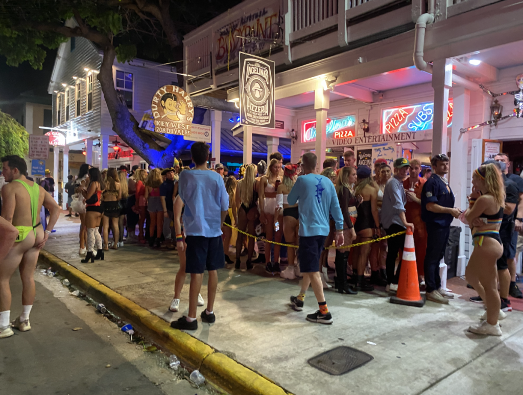 A large group of people, several identified as University of Miami students, wait in line outside Durty Harry's on Duval Street in Key West on Saturday, Oct. 31.