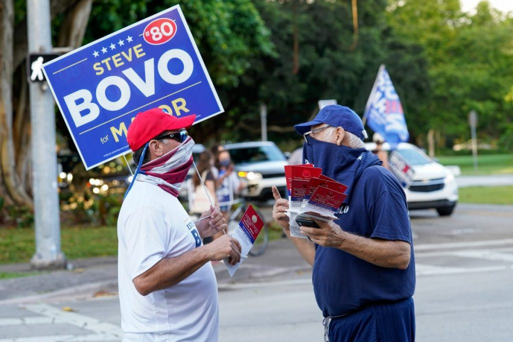 A Bovo supporter takes campaign literature from a supporter of Frank Polo, a republican write-in candidate seeking to represent Florida's 27th congressional district, at an intersection near the Coral Gables Library on Tuesday, Nov. 3.