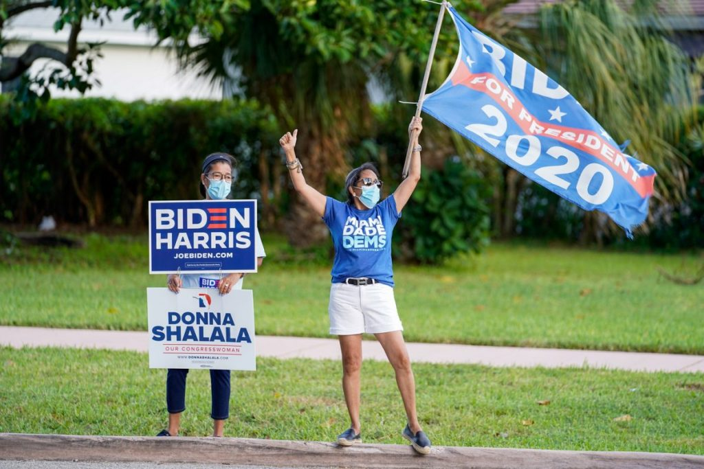 Two democratic supporters hold campaign signs at an intersection near the Coral Gables Library on Tuesday, Nov. 3.