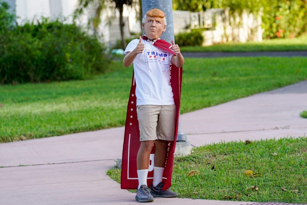 A Trump supporter wearing a Trump mask, shirt, and cape gives a thumbs-up at an intersection near the Coral Gables Library on Tuesday, Nov. 3.