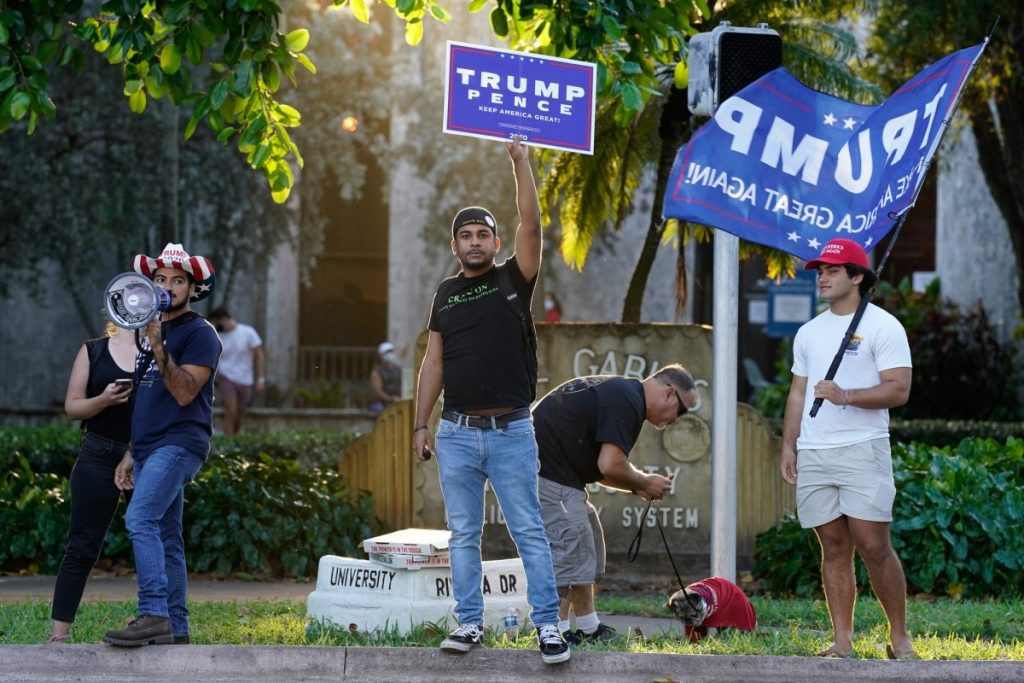 Trump supporters fly flags and hold campaign signs at an intersection near the Coral Gables Library on Tuesday, Nov. 3.
