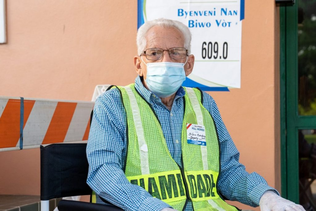 Silvio Cordova, a deputy poll worker, sits at the entrance to the Coral Gables Community Center on Tuesday, Nov. 3.