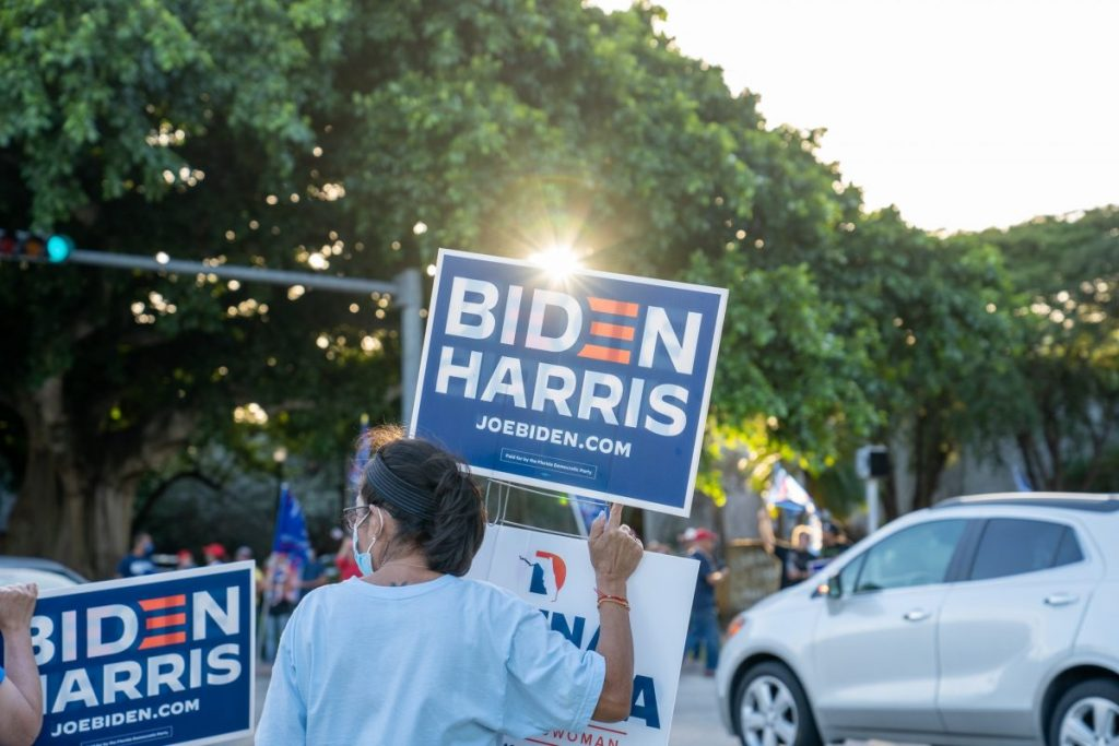 Biden supporters hold campaign signs at an intersection near the Coral Gables Library on Tuesday, Nov. 3.