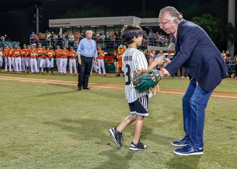 Morris congratulates his son, Will, after he throws the ceremonial first pitch after Morris' jersey number retirement ceremony in 2019. Known as Number 3, the longtime coach now prioritizes being a family man.