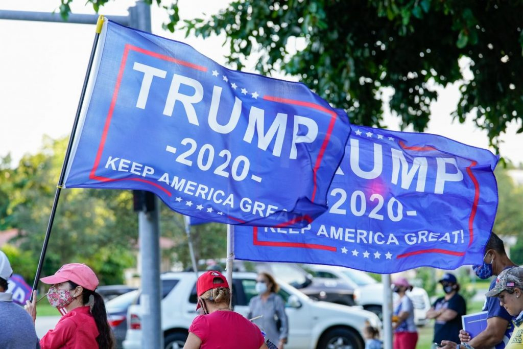Trump supporters fly Trump campaign flags in a show of support for the president at an intersection near Coral Gables Library on Tuesday, Nov. 3.