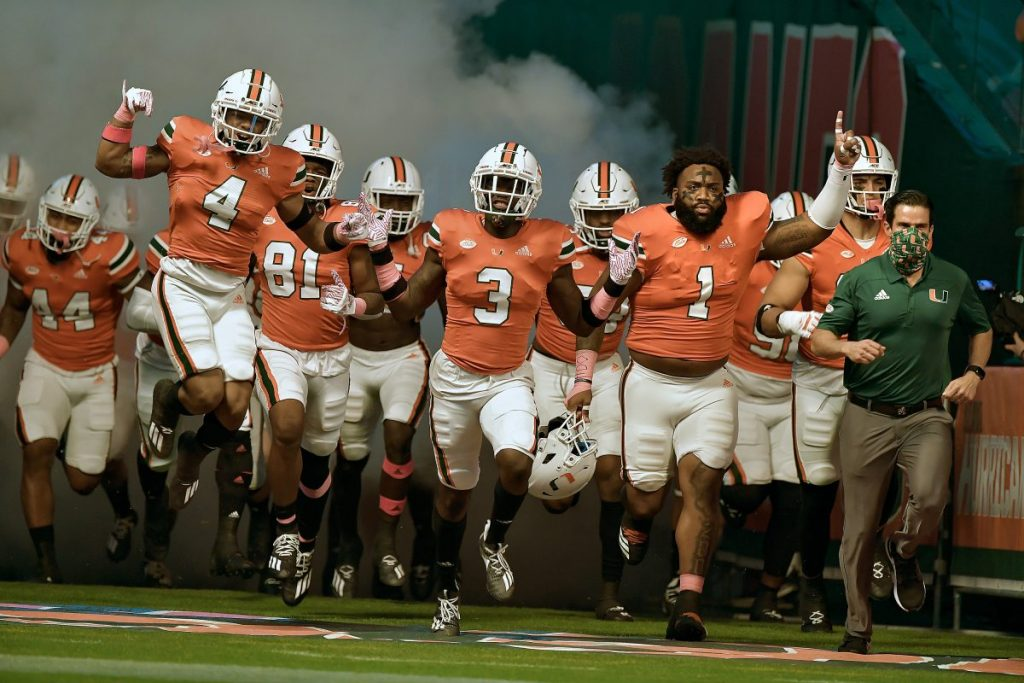 The Miami Hurricanes run on the field before their game versus Virginia on Oct. 24, 2020.