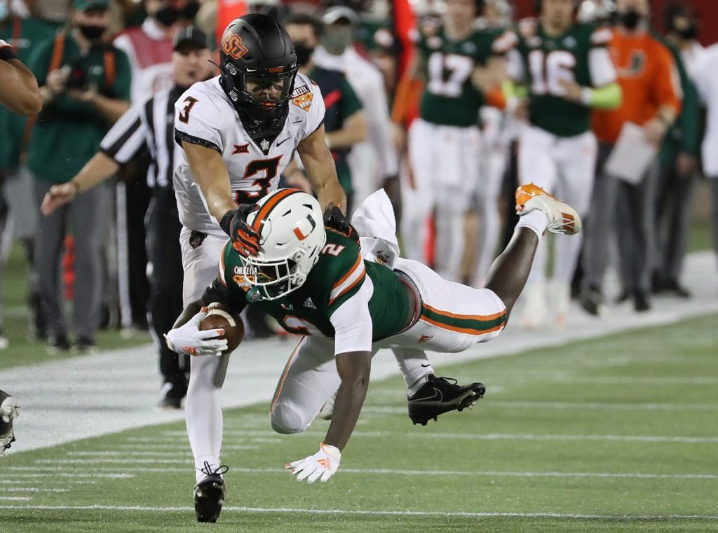 Miami running back Donald Chaney Jr. (2) leaps for extra yardage under OK State safety Tre Sterling (3) during the Cheez-It Bowl at Camping World Stadium in Orlando on Tuesday, December 29, 2020.