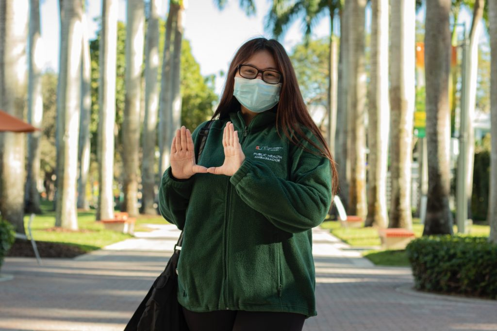"""Freshman Public Health Ambassador Maddie Shewmaker throws up the """"U"""" outside of Richter Library on Feb. 3. PHAs are assigned  to five different zones on campus."""