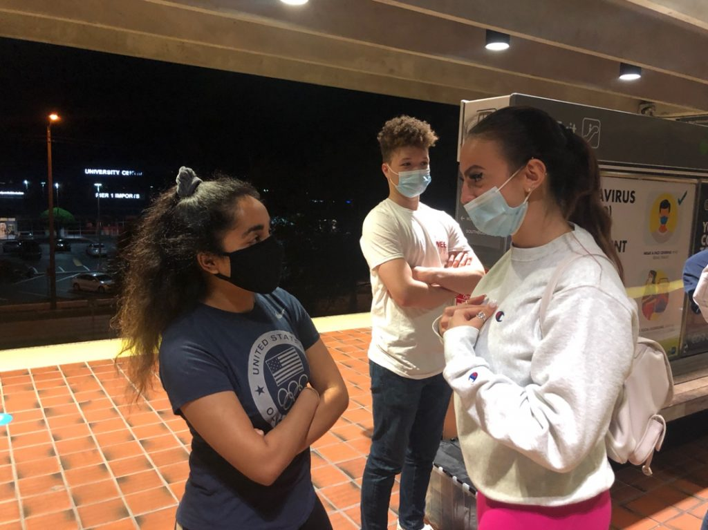 STEP e-board members Preeti Shukla, left, and Nicole Ivanova, right, speak about STEP's volunteer event while waiting for the metro to arrive with STEP volunteer Joseph Wicker on March 19 at University Metrorail Station.
