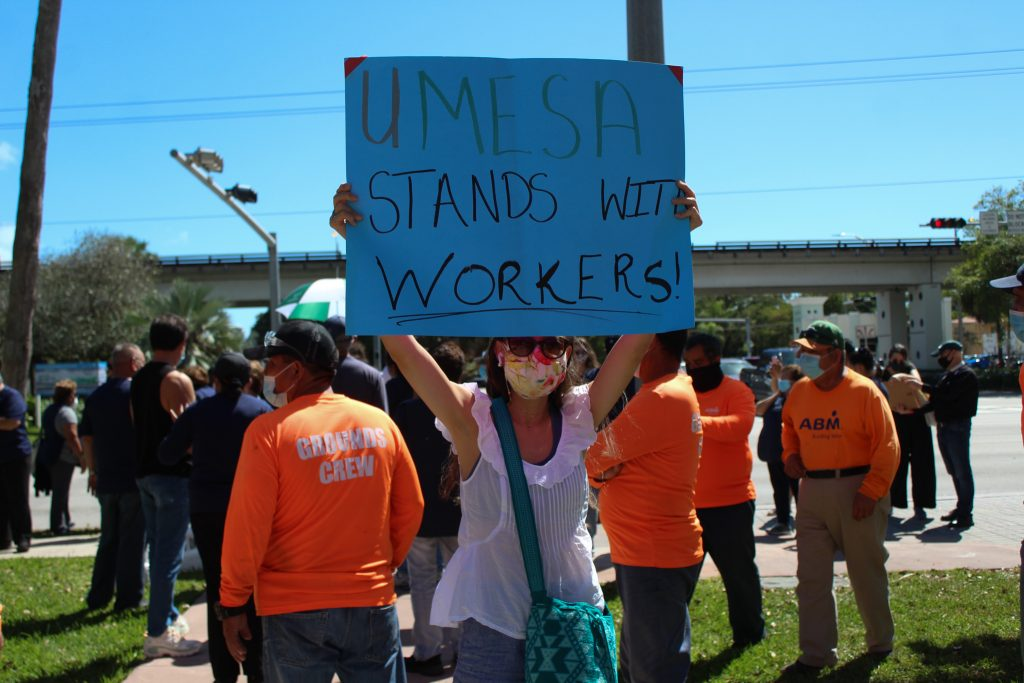 A member of UMESA protests the current working conditions of the ABM janitorial staff Feb. 26. Protesters began at St. Bebe Episcopal Chapel and marched to Ponce De Leon Boulevard.