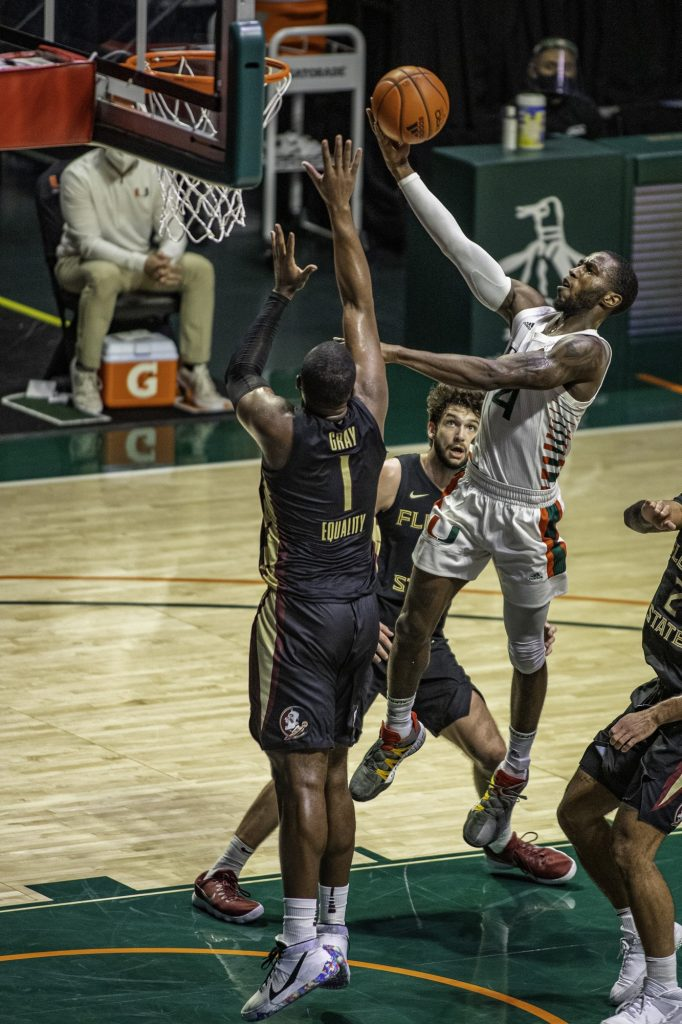 Senior Elijah Olaniyi attempts to make a layup over a Florida State defender in Miami's loss on Wednesday Feb. 24 at the Watsco Center. Miami finished the season with a 10-17 record while only winning four of their 19 conference games.