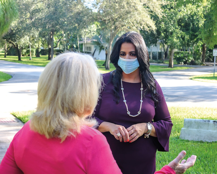 Claudia Miro talks with a voter in Coral Gables.