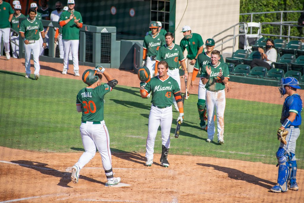Gabe Rivera (43) greets teammate Alex Toral (30) after the first baseman hit a home run against FGCU on April 14 at Mark Light Field.