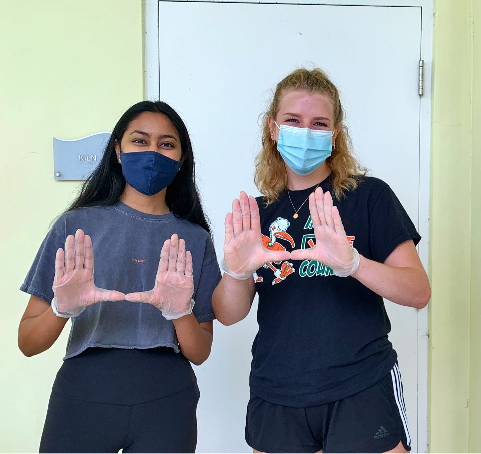 Melanie Veerasammy (left) and Jill Ingram (right) take a break from bleaching and washing shower curtains at the Lotus House to throw up the U.