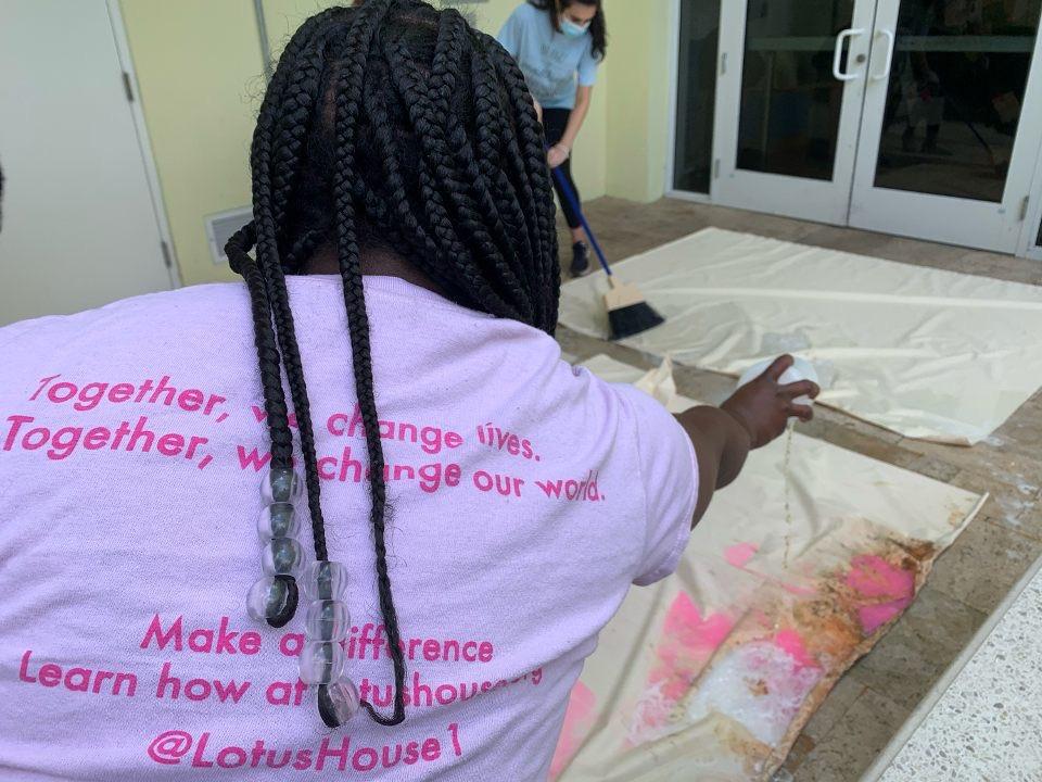 Hadieh Zolfahari helps Lotus House staff scrub down a shower.