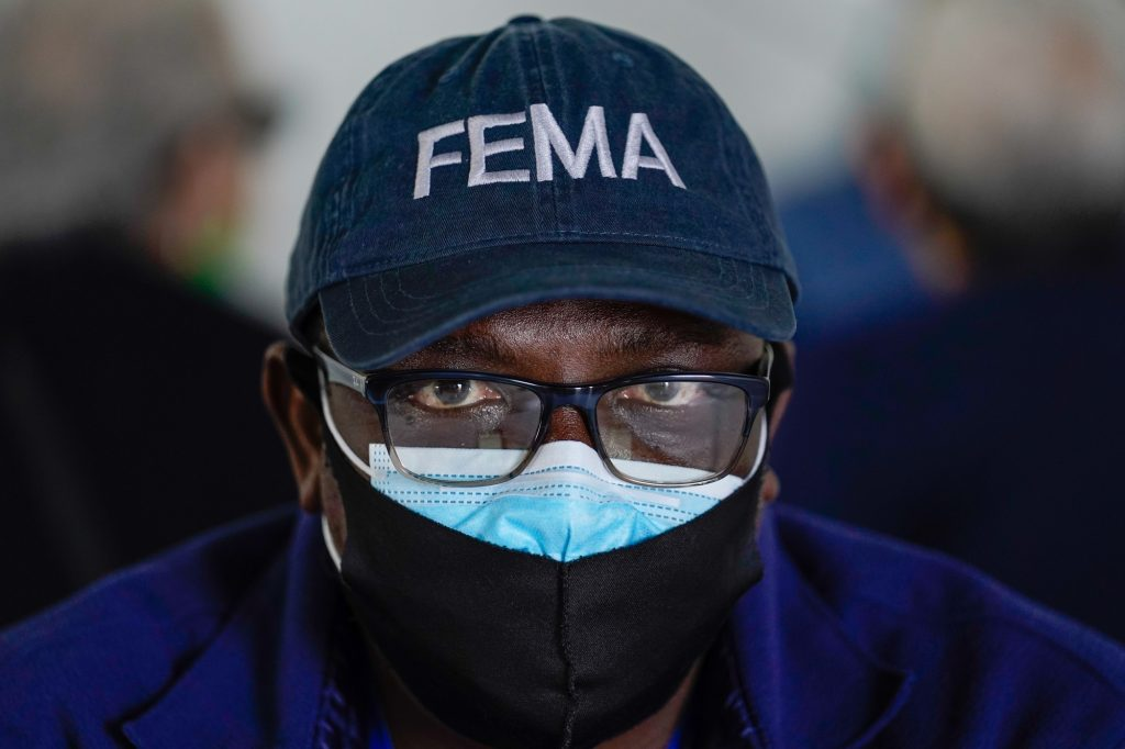 Oladipupo Salau, an emergency management specialist with FEMA, sits at a table in the first registration tent at the FEMA Miami Dade College North Campus vaccination site on March 21, 2021.