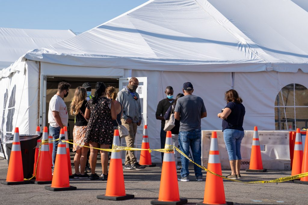 People seeking vaccination speak with site employees to confirm eligibility before being sent to the registration tent at the Federal Emergency Management Agency Miami Dade College North Campus vaccination site on March 21, 2021.