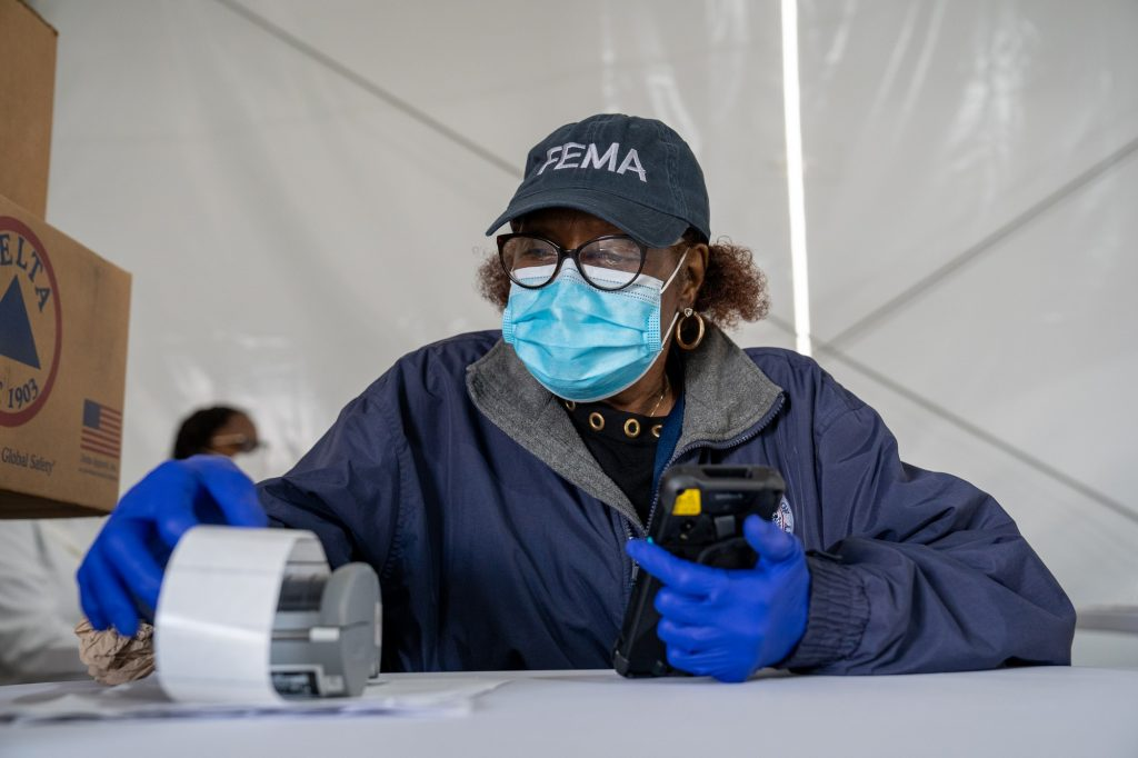 Faye York, a FEMA employee, waits to register people in the second registration tent at the FEMA Miami Dade College North Campus vaccination site on March 21, 2021.