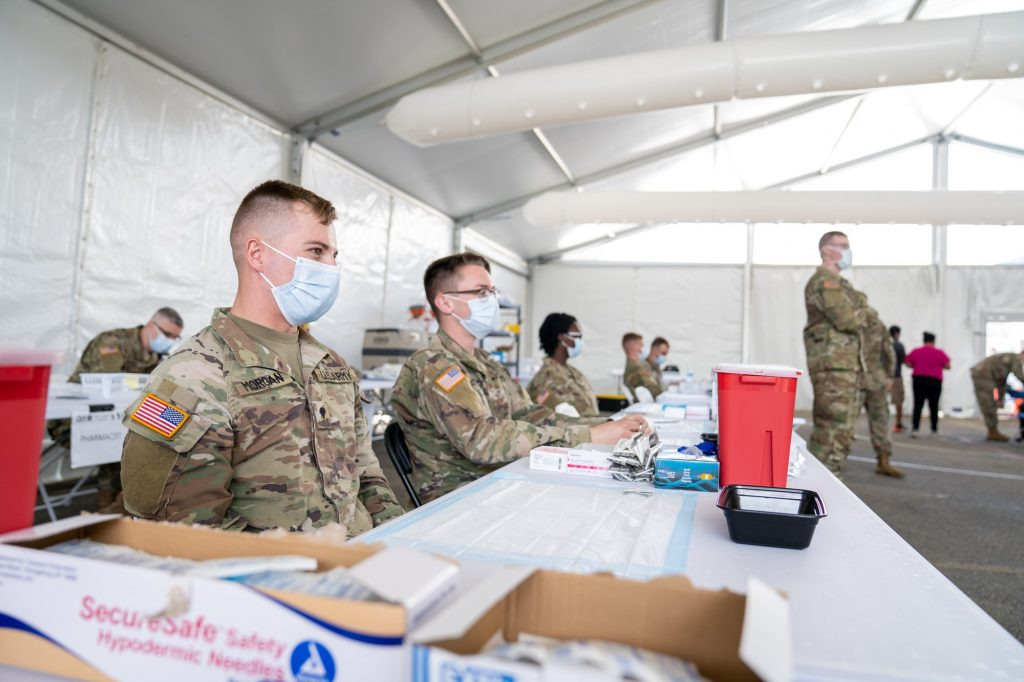 Members of the U.S. military wait to vaccinate Florida residents in the vaccination tent at the FEMA Miami Dade College North Campus vaccination site on March 21, 2021. 139 soldiers from Fort Riley, Kansas, were deployed to the site as a part of joint military assistance to state-run, federally supported community vaccination centers, according to a March 1 U.S. Army Public Affairs release.