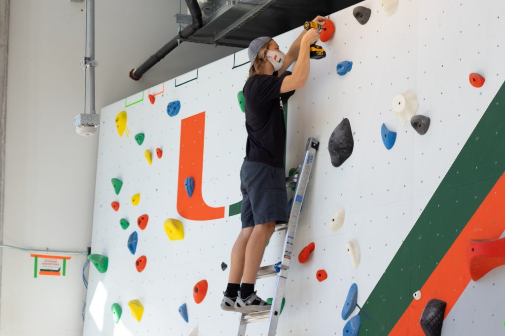Sophomore Trey Riera-Gomez adjusts the course at the new climbing/bouldering wall in Lakeside Village on Oct. 14, 2020. The climbing wall is open to all members of the UM community.