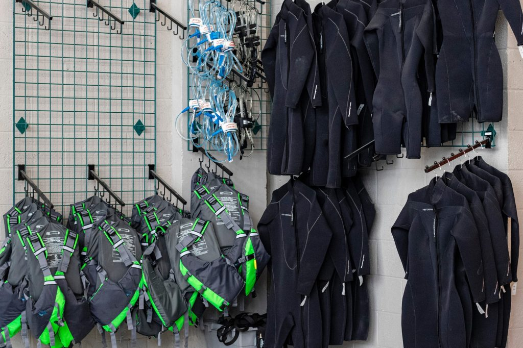 Wetsuits, lifejackets, and other aquatic equipment hang on the walls of Outdoor Adventures April 5. Rental equipment can be reserved by any member apart of the UM community.