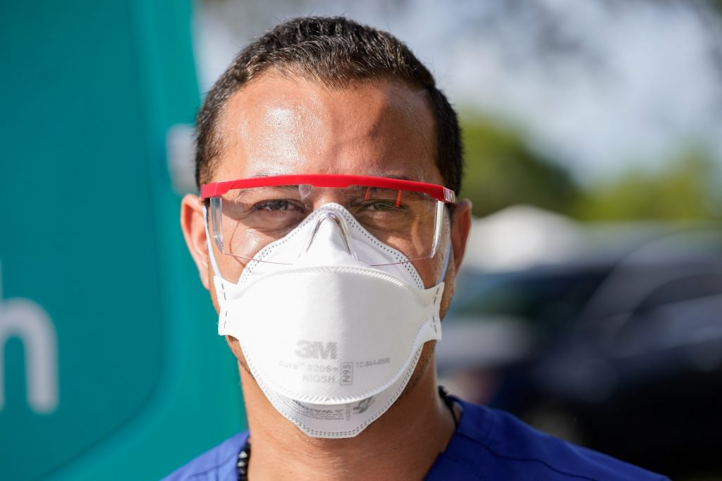 Emergency Medical Technician Jackson Salazar wears personal protective equipment at a county-supported pop up site at Homestead Air Reserve Park, on Wednesday, March 31, 2021.