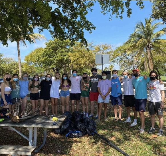 Esther Cai, middle with black mask and green shirt, poses with members of fraternity Lambda Chi Alpha and sorority Tri Delta after they collected more than 100 pounds of trash at a beach cleanup on March 20 at Crandon Beach. Photo Credit: Dawei Shao