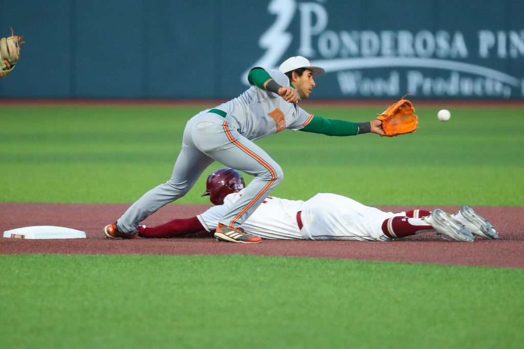 Anthony Vilar attempts to catch the baseball at second base while a Boston College slides into the base. The Hurricanes lost 13-0 at