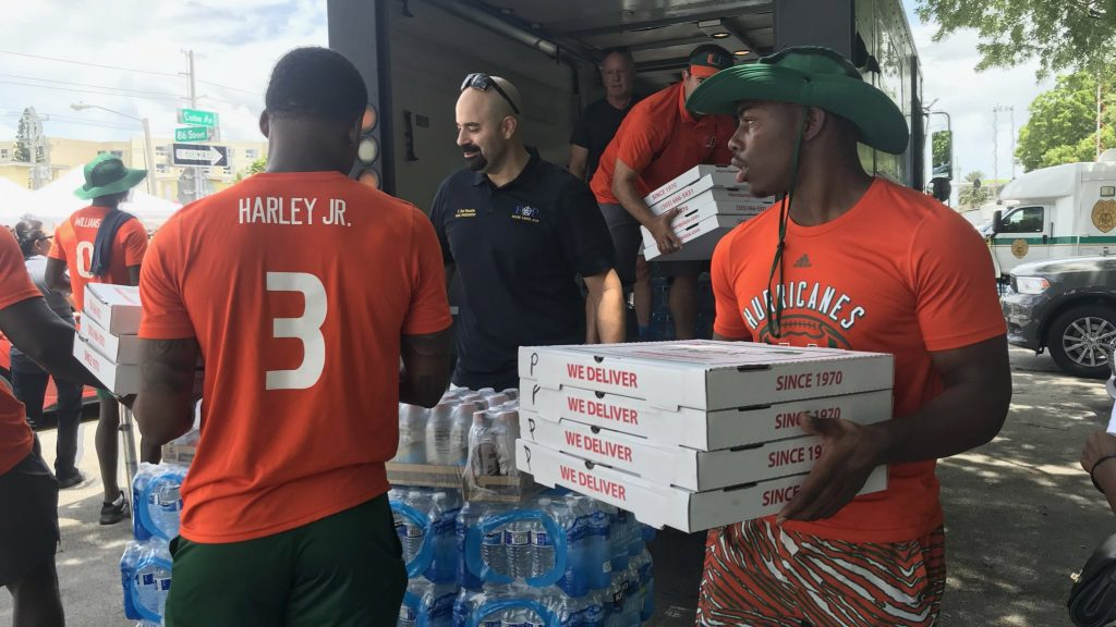Kamren Kinchens (right) and Mike Harley Jr. (left), carry boxes of pizza out of a truck in Surfside, Fl.