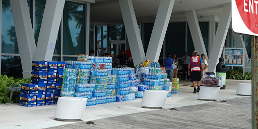 Water bottles and snacks line the entrance to the Town of Surfside Community Center on Saturday, June 27, as a Red Cross volunteer makes his way toward the building's front door. The center was repurposed to support individuals impacted by the Thursday collapse of Champlain Towers South.