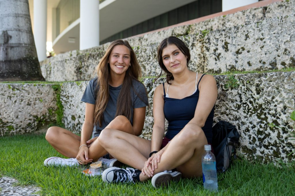Freshmen Valentina Urbicain and Isabel Briones, majoring in Architecture and Broadcast Journalism respectively, sit by Lake Osceola on Aug. 19, 2021.