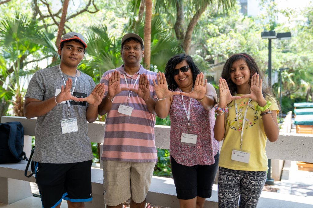 Yasith Yapa (left) and family throw up the U while moving into Hecht Residential College on Aug. 17, 2021.