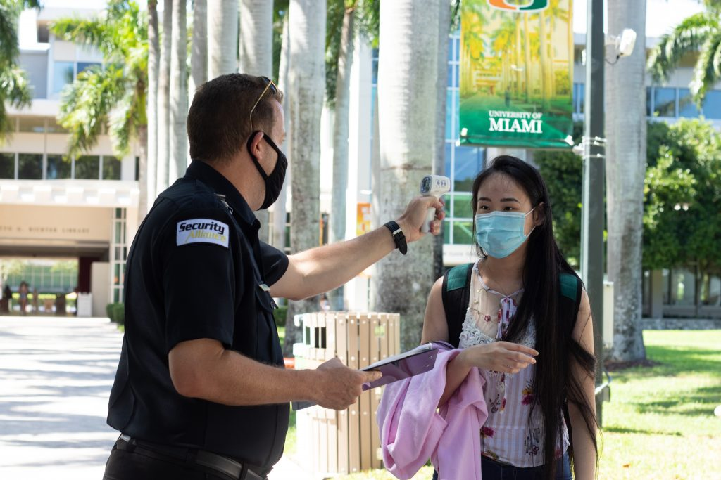 A University of Miami student has her temperature taken by a Security Alliance worker. With UM preparing for a fully in-person fall semester, students have many questions they would like answered by administrators at the virtual town hall on August 11.