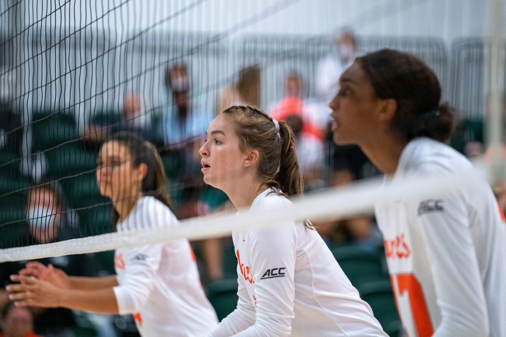 Freshman middle blocker Ashley Carr and teammates prepare for the serve during the Canes' game versus UMBC in the Knight Sports Complex on Aug. 29, 2021.