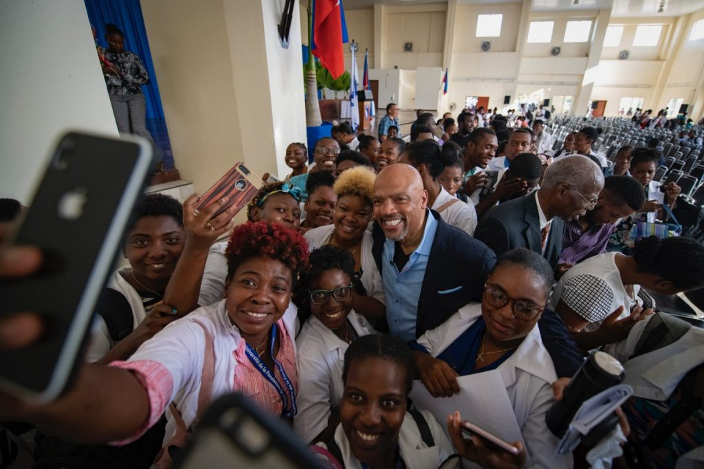Dean Henri Ford, center, poses for a photo with people in Haiti.Ford is a Haitian-born pediatric surgeon who maintains close ties with his native country. In 2010 he traveled to Haiti after the earthquake to provide surgical care to children injured in the disaster. Ford regularly returns to Haiti to provide medical care to its residents.