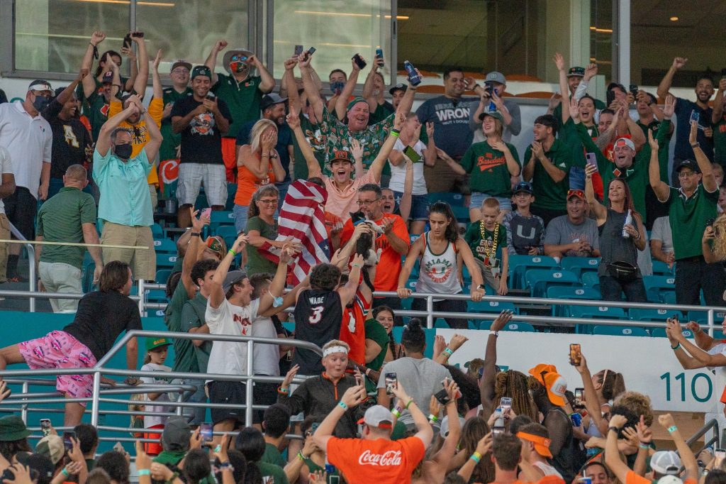 Fans celebrate after a cat survived a fall from the 300 level seating area, aided by an American flag outstretched by UM fans, during the first half of Miami's game versus Appalachian State at Hard Rock Stadium on Sept. 11, 2021.