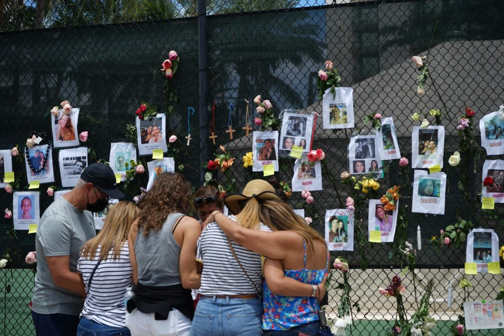 A family huddles close at the Surfside Tennis Center on Saturday, June 26. The center's gate has been used as a memorial wall for those lost in the collapse.