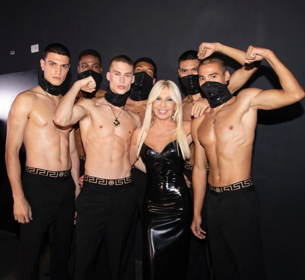 Donatella Versace poses with models for the Versace brand