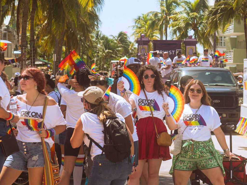 Supporters of the LGBTQIA+ community in Miami Beach celebrate with colorful gear along Ocean Drive