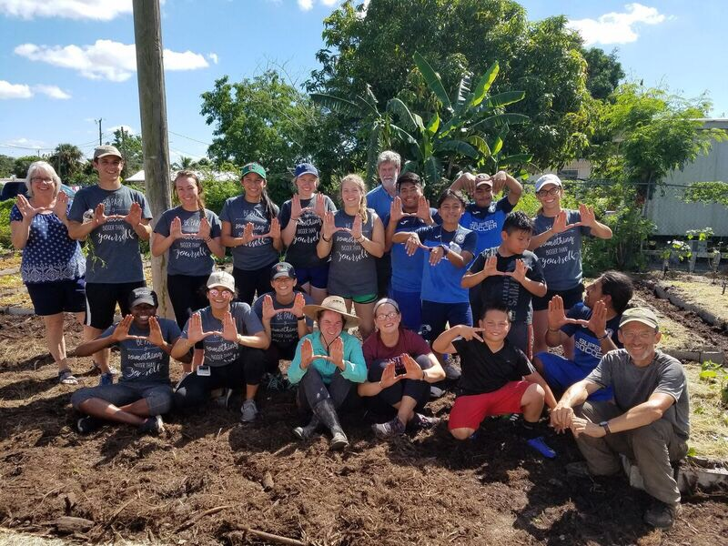 """UM students throw up the """"U"""" after a long day of planting vegetables with Cultivate Abundance in Immokalee, FL, in 2018."""