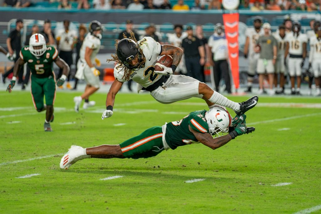Junior safety Gurvan Hall, Jr. tackles wide receiver Corey Sutton during Miami's game versus Appalachian State at Hard Rock Stadium on Sept. 11, 2021.